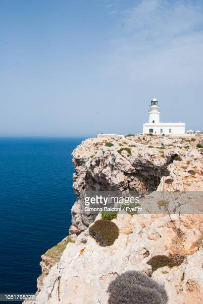 lighthouse on rock by sea against sky - ミノルカ ストックフォトと画像