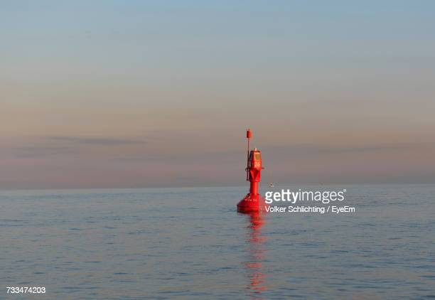 lighthouse on sea against sky during sunset - buoy stock photos and pictures