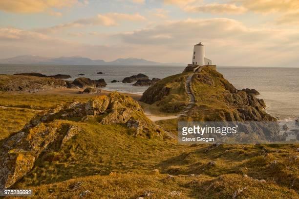 Lighthouse on seashore at sunset
