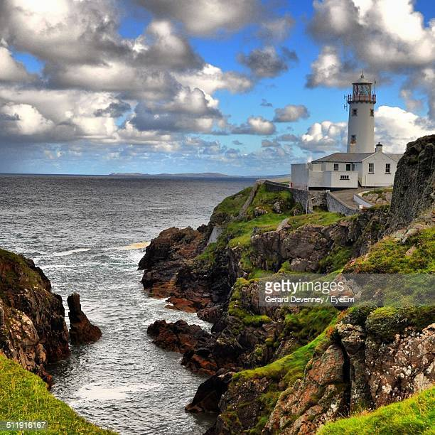 lighthouse on shore against calm sea - belfast stock pictures, royalty-free photos & images