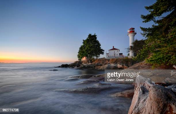 Lighthouse on shore of Pacific Ocean at sunset
