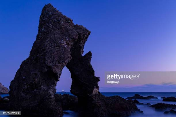 a lighthouse on the island through the bizarre rock against sky during sunset - isogawyi stock pictures, royalty-free photos & images