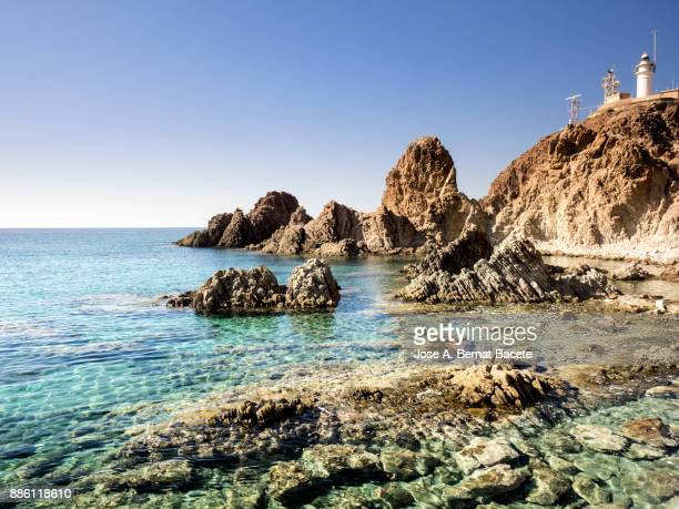 lighthouse on the sea a sunny day on the beach and rocky coast of the cabo de gata with formations of volcanic rock. cabo de gata - nijar natural park, sirens reef, beach, biosphere reserve, almeria,  andalusia, spain - biosphere planet earth stock photos and pictures