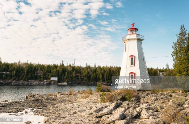 lighthouse overlooking big tub harbour, tobermory, ontario - ontario canada stock pictures, royalty-free photos & images