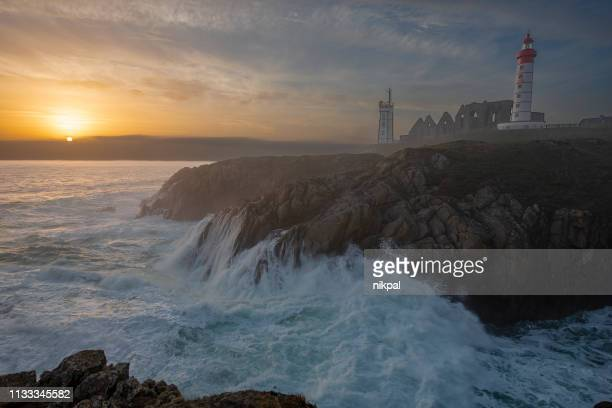 lighthouse pointe de saint-mathieu, sunset big waves, brittany (bretagne), france - finistere stock photos and pictures