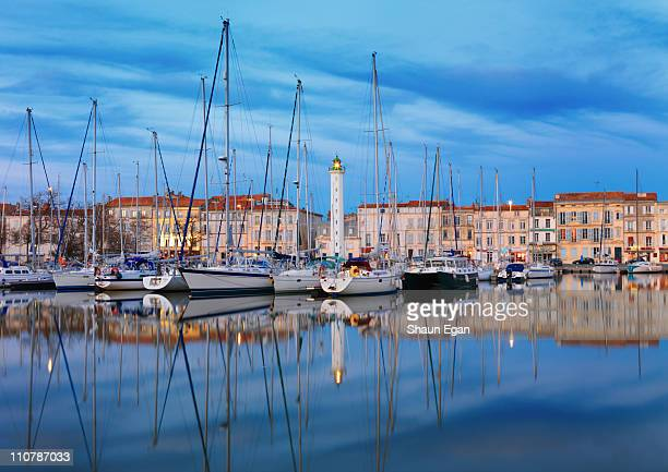 lighthouse reflected in harbour at dusk - la rochelle stock pictures, royalty-free photos & images
