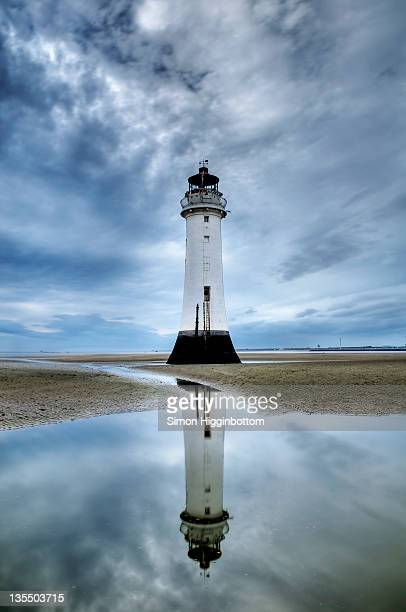 lighthouse reflection in sea, new brighton - simon higginbottom stock pictures, royalty-free photos & images