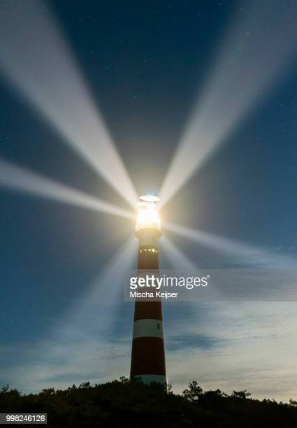 lighthouse rotating beams at night, island of ameland, hollum, friesland, netherlands - leuchtturm stock-fotos und bilder