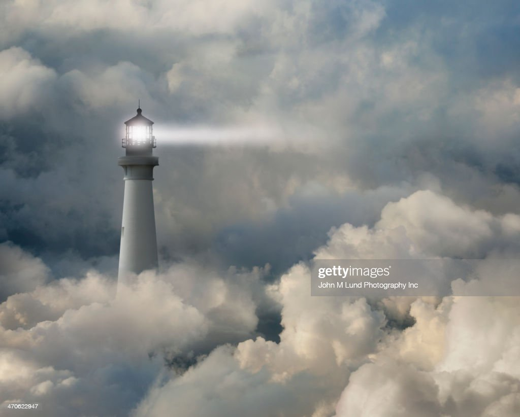 Lighthouse shining beam into thick clouds : Stock Photo