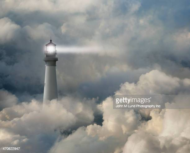lighthouse shining beam into thick clouds - guidance stock pictures, royalty-free photos & images
