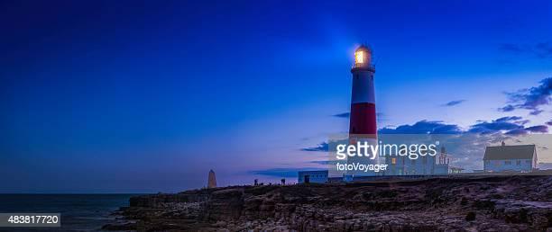 Lighthouse shining over ocean shore sunset Portland Bill Dorset UK