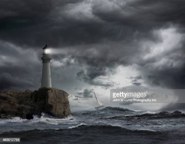 Lighthouse shining over stormy ocean