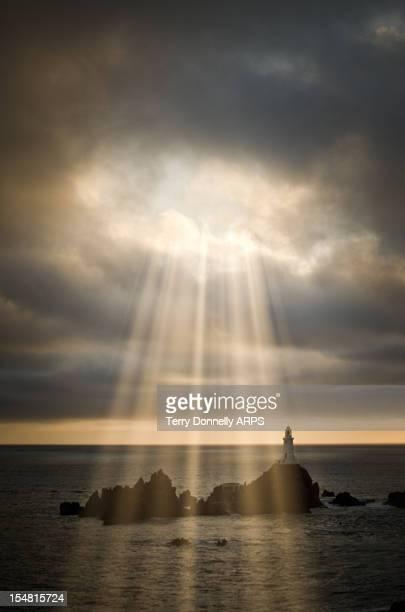 Lighthouse under stormy sky with sundays