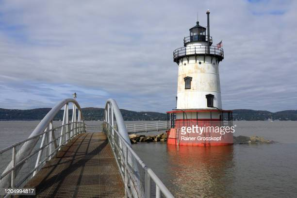 a lighthouse with a red base and a white tower in the hudson river - rainer grosskopf foto e immagini stock