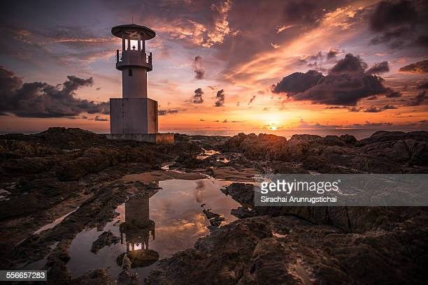 A lighthouse with light rays at sunset