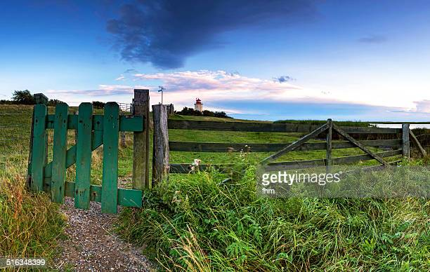 lighthouse with wooden gate in foreground - fehmarn stock-fotos und bilder