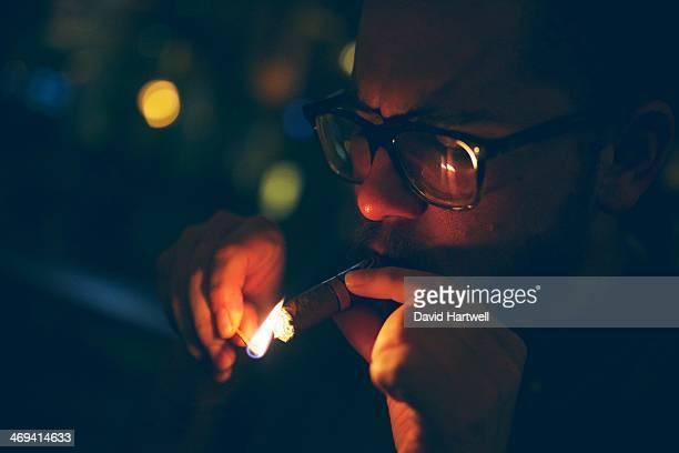 Lighting a cigar with a match