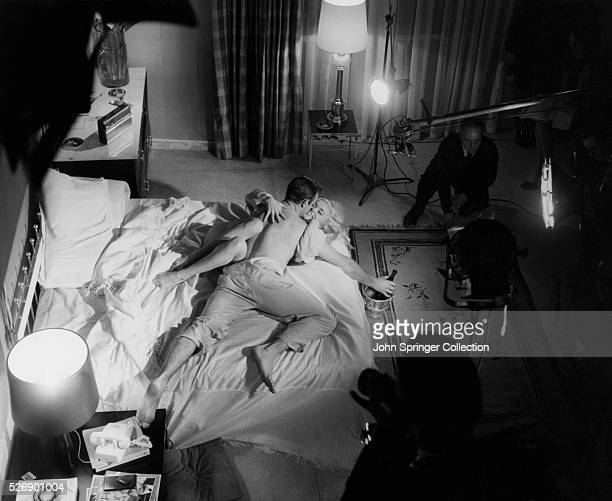 Lighting and film crew working with Sean Connery and Shirley Eaton in a bedroom scene of Goldfinger