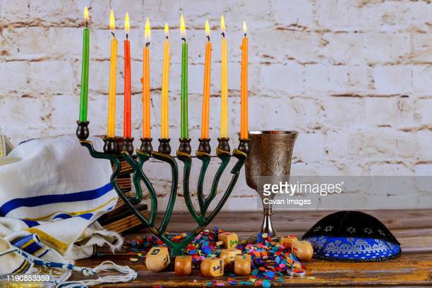 lighting candles in menorah for hanukkah - hannukkah stock pictures, royalty-free photos & images