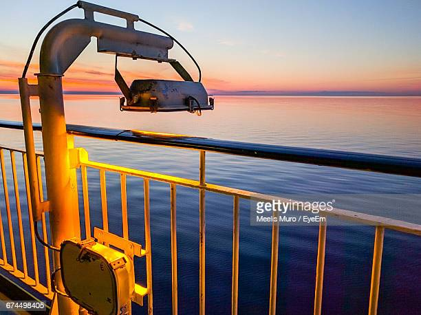 lighting equipment by railing of cruise ship in sea during sunset - muro stock photos and pictures
