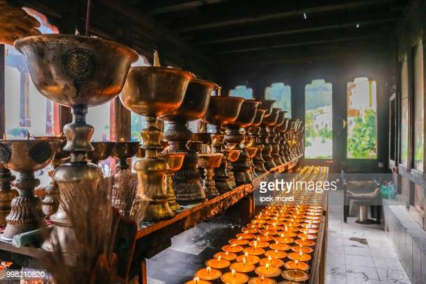 lighting of praying candles in zangdhopelri monastery in thimphu - ipek morel stock pictures, royalty-free photos & images