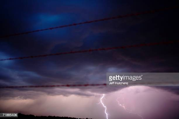 Lighting strikes through a fence and across a field as Tempest Tours storm chase tour guests watch a storm over the Great Plains in the United States...