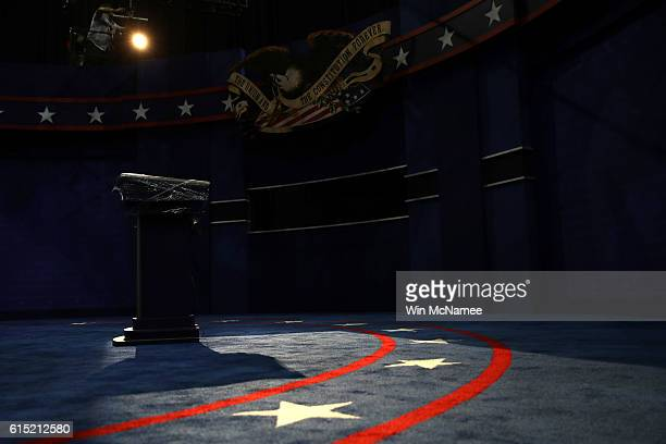 Lighting technicians adjust lighting on the lecterns to be used by Democratic presidential candidate Hillary Clinton and Republican presidential...