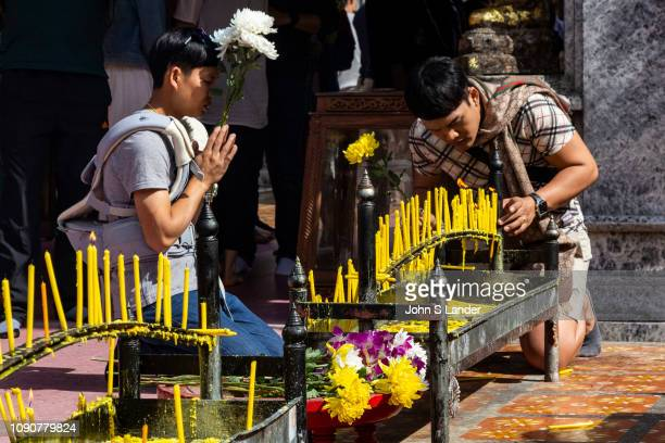 Lighting Votive Candles at Wat Doi Suthep its official name Wat Phrathat Doi Suthep is a Theravada Buddhist temple in Chiang Mai Thailand The temple...