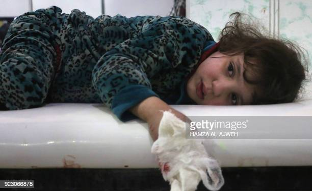 A lightly wounded Syrian girl lies on a stretcher at a makeshift clinic following Syrian government bombardments in Douma in the besieged Eastern...