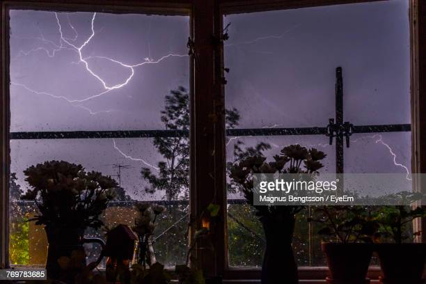 Lightning Against Sky Seen Through Window At Home