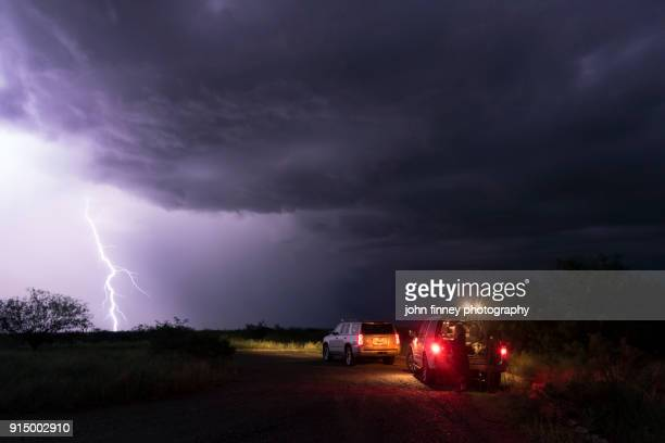 Lightning bolt hits the ground with storm chasers watching, Arizona, USA.