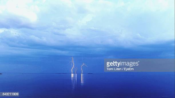 Lightning Bolts At Sea Against Cloudy Sky