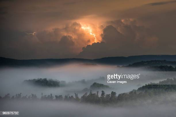 lightning clouds over forest and mountain at night - arkansas stock pictures, royalty-free photos & images