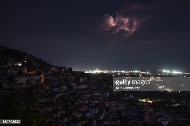 Lightning flashes illuminate the clouds over the sea on the coast of the Haitian capital PortauPrince during an early morning thunderstorm on October...