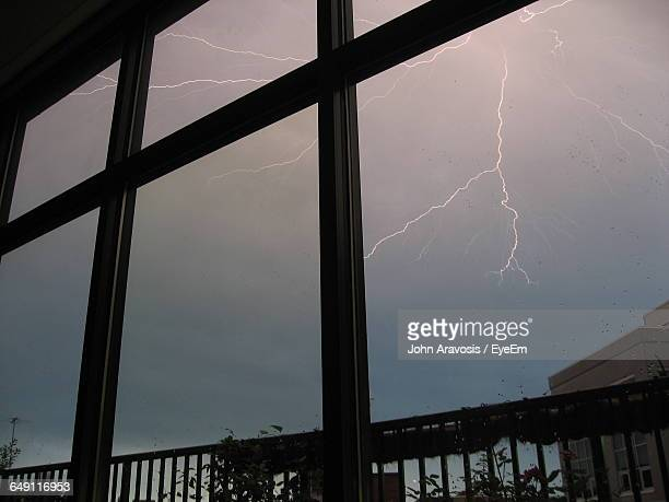 Lightning In Sky At Dusk Seen Through Glass Window