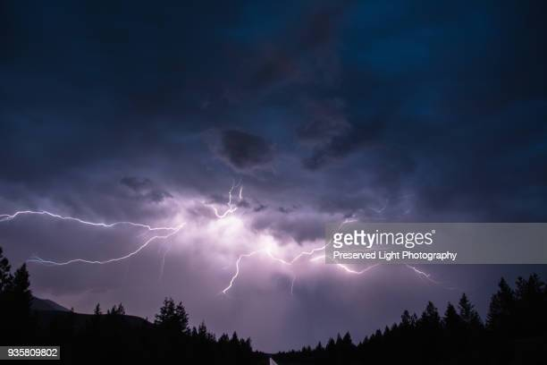 lightning in sky over canadian rocky mountains, kootenay region, fernie, british columbia, canada - ominous stock photos and pictures