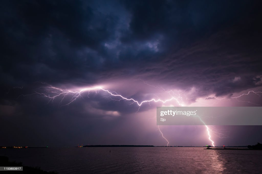 Lightning in the dark night sky over a lake during summer : Stock Photo
