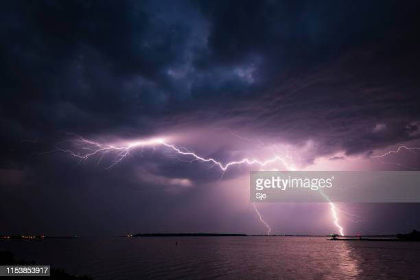 lightning in the dark night sky over a lake during summer - hurricane storm stock pictures, royalty-free photos & images