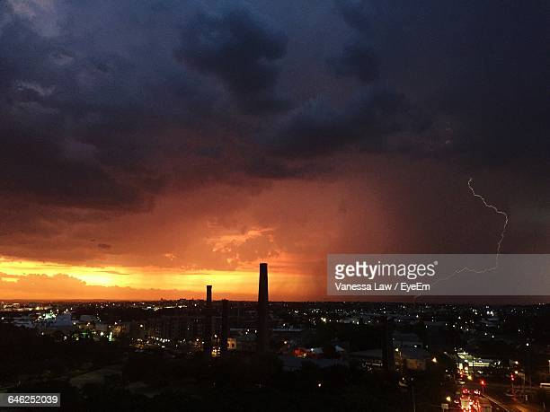 Lightning Over Cityscape Against Cloudy Sky During Sunset