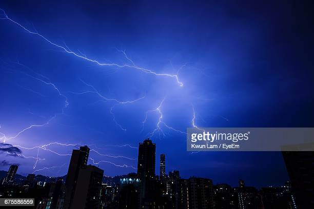 Lightning Over Cityscape Against Sky At Night