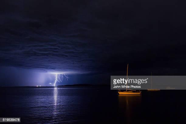 Lightning over moored yacht.