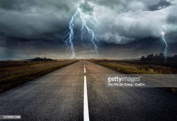lightning over road during sunset - lightning stock pictures, royalty-free photos & images