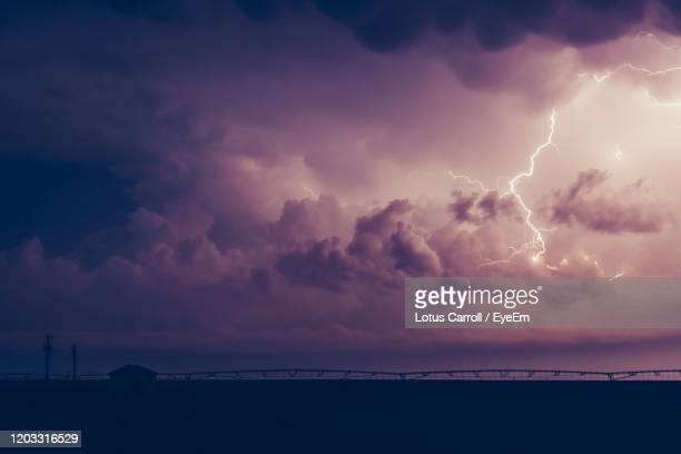 lightning over sea against sky during sunset - country texas lightning stock pictures, royalty-free photos & images