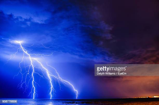 lightning over sea against sky - lightning stock pictures, royalty-free photos & images