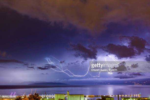lightning over trees against sky at night - drazen stock pictures, royalty-free photos & images