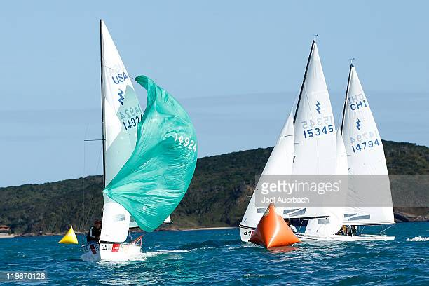 Lightning skippered by Jeff Coppens of the USA sets its spinnaker as they round the windward mark ahead of Lightning skippered by William Brown of...