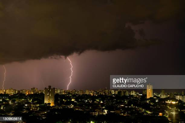 lightning storm over city during night - claudio capucho stock pictures, royalty-free photos & images