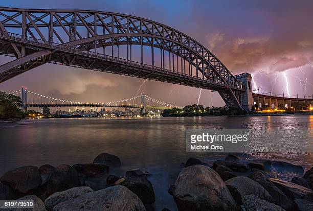 Lightning storm over the Hell Gate Bridge and Triborough RFK Bridge with manhattan skyline in the background. East River. Astoria Park. NYC.