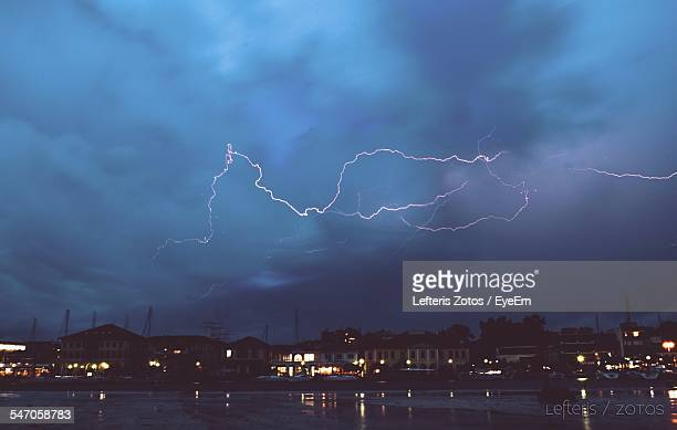 Lightning Strike Above Silhouette Built Structures And River