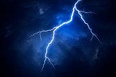 A lightning strike on a cloudy dramatic stormy sky